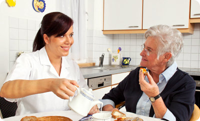 caregiver and old woman in the kitchen