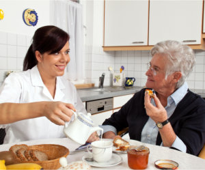 elder having breakfast with caregiver